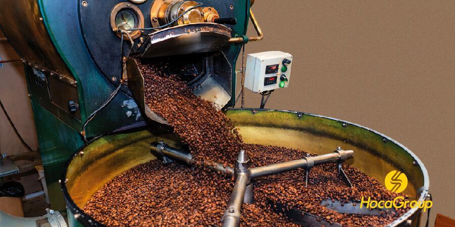 Cà phê mới rang từ trống rang cà phê tràn vào khay làm mát.